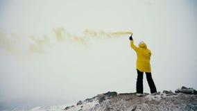 El adolescente joven que juega con humo señala por medio de luces en un top de montañas metrajes