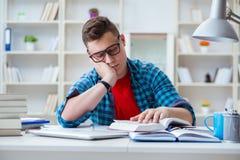 El adolescente joven que se prepara para los exámenes que estudian en un escritorio dentro Fotos de archivo