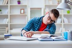 El adolescente joven que se prepara para los exámenes que estudian en un escritorio dentro Imagen de archivo libre de regalías