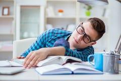 El adolescente joven que se prepara para los exámenes que estudian en un escritorio dentro Imagenes de archivo