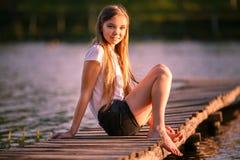 El adolescente joven que se sienta en el embarcadero en puesta del sol emite Foto de archivo