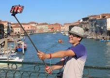 El adolescente joven toma una imagen por su smartphone en el bridg Imagen de archivo