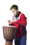 El adolescente juega el djembe en estudio con el fondo blanco Foto de archivo libre de regalías