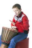 El adolescente juega el djembe en estudio con el fondo blanco Fotografía de archivo libre de regalías