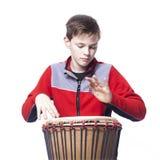 El adolescente juega el djembe en estudio con el fondo blanco Imagenes de archivo