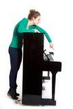 El adolescente juega el piano en camisa verde Imágenes de archivo libres de regalías