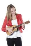 El adolescente juega el ukelele en estudio contra el fondo blanco Foto de archivo