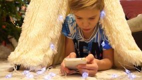 El adolescente juega en el smartphone en el cuarto de niños en una tienda con una luz de la Navidad Niñez feliz almacen de video