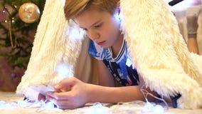 El adolescente juega en el smartphone en el cuarto de niños en una tienda con una luz de la Navidad Niñez feliz almacen de metraje de vídeo