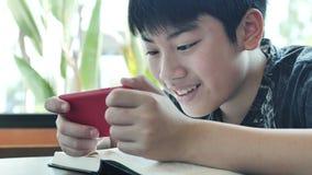 El adolescente juega a juegos en el tel?fono m?vil almacen de metraje de vídeo