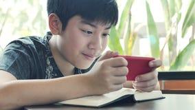 El adolescente juega a juegos en el tel?fono m?vil almacen de video
