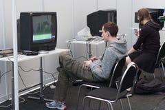 El adolescente juega la consola del juego con la televisión en Animefest Imágenes de archivo libres de regalías
