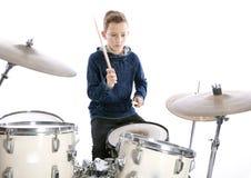 El adolescente juega los tambores en estudio Imagenes de archivo