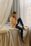 El adolescente laughting está hablando en el teléfono móvil mientras que se sienta en la cama La foto integral Fotografía de archivo libre de regalías
