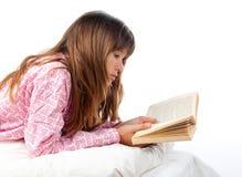 El adolescente lee el libro en cama Foto de archivo