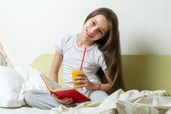 El adolescente lee el libro y el zumo de naranja de los controles Fotografía de archivo