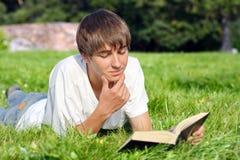 El adolescente lee un libro Foto de archivo libre de regalías