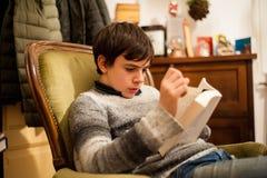 El adolescente lee un libro en la butaca en casa Imágenes de archivo libres de regalías