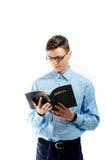 El adolescente leyó y estudia de la biblia grande del libro con el aislador de las lentes Imagenes de archivo