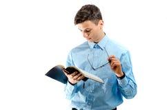 El adolescente leyó y estudia del libro negro con las lentes aisladas Imágenes de archivo libres de regalías