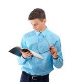 El adolescente leyó y estudia del libro negro con las lentes aisladas Imagen de archivo