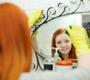 El adolescente limpia el espejo con la esponja Foto de archivo