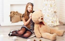 El adolescente lindo abraza un oso de peluche suave grande en el ingenio interior Fotografía de archivo libre de regalías