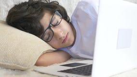 El adolescente lindo del muchacho que lleva los vidrios duerme en el sof? al lado del ordenador port?til 4K almacen de video