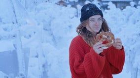 El adolescente lindo divertido come el pretzel en invierno metrajes