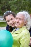 El adolescente lindo está abrazando a su abuelita sonriente hermosa en mejilla imagenes de archivo
