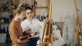 El adolescente lindo está aprendiendo la pintura del profesor experimentado en escuela de arte en taller con las ilustraciones y  almacen de metraje de vídeo