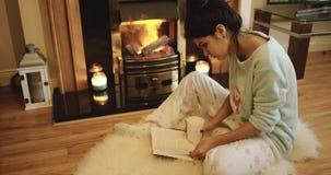 El adolescente lindo está leyendo un libro al lado de la chimenea Epopeya roja 4K metrajes