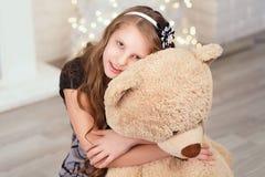 El adolescente lindo joven abraza un oso de peluche suave grande en el interi Imagen de archivo libre de regalías