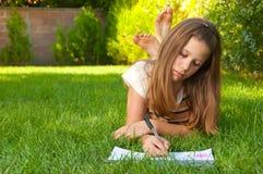 El adolescente lindo miente en la hierba y drena Foto de archivo