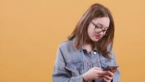 El adolescente lindo que manda un SMS en su smartphone y parece impaciente almacen de video