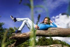 El adolescente lindo se acuesta en la madera Foto de archivo libre de regalías