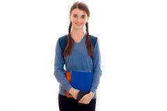 El adolescente lindo se coloca con las coletas en la chaqueta azul que celebra una carpeta y una sonrisa Fotografía de archivo libre de regalías