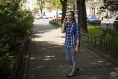 El adolescente llama en un teléfono celular que se coloca en el callejón verde El caminar Fotografía de archivo