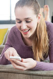 El adolescente magnífico de risa conectó con su envío de mensajes de texto del smartphone Imágenes de archivo libres de regalías