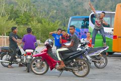 El adolescente malasio con sus amigos felices recolecta en el término de autobuses por la tarde Foto de archivo libre de regalías