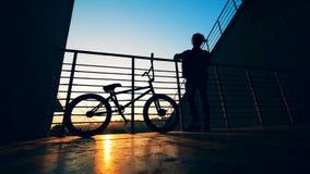 El adolescente masculino está ensuciando con su pelo mientras que se coloca en una plataforma con su bici en la puesta del sol almacen de metraje de vídeo