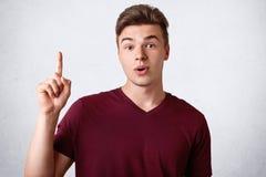 El adolescente masculino pasmado con la expresión sorprendida mantiene el finger delantero aumentado, vestido camiseta casual, ti Imagenes de archivo