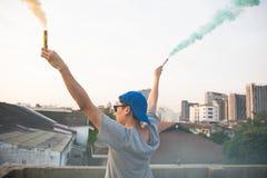 El adolescente masculino que sostiene humo colorido se pega para arriba en el aire sobre fondo urbano de la ciudad Fotografía de archivo