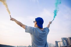 El adolescente masculino que sostiene humo colorido se pega para arriba en el aire sobre fondo urbano de la ciudad Imágenes de archivo libres de regalías