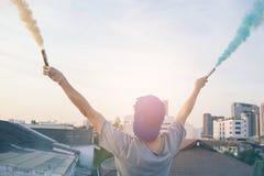 El adolescente masculino que sostiene humo colorido se pega para arriba en el aire sobre u Fotografía de archivo libre de regalías