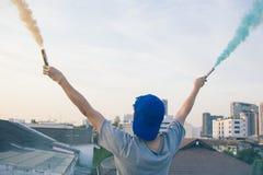 El adolescente masculino que sostiene humo colorido se pega para arriba en el aire sobre u Fotos de archivo libres de regalías
