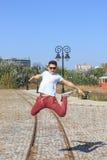 El adolescente masculino salta en parque retro y gafas de sol que llevan Fotografía de archivo libre de regalías