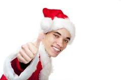 El adolescente masculino sonriente de Papá Noel muestra el pulgar para arriba Imagenes de archivo