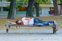 El adolescente miente en el banco en el parque Imagen de archivo
