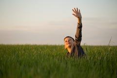 El adolescente miente en la hierba alta en la puesta del sol Imagenes de archivo